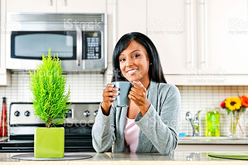Woman in kitchen with coffee cup royalty-free stock photo