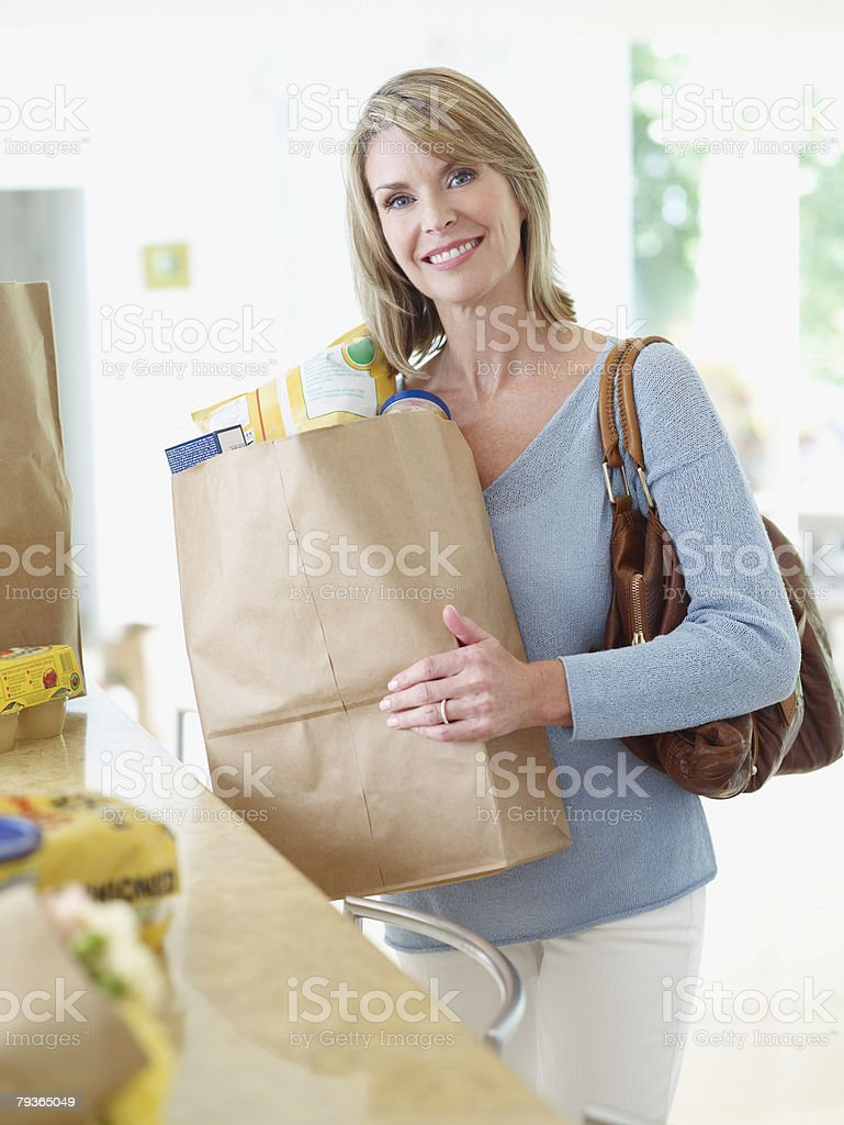 Woman in kitchen with grocery bags royalty-free stock photo