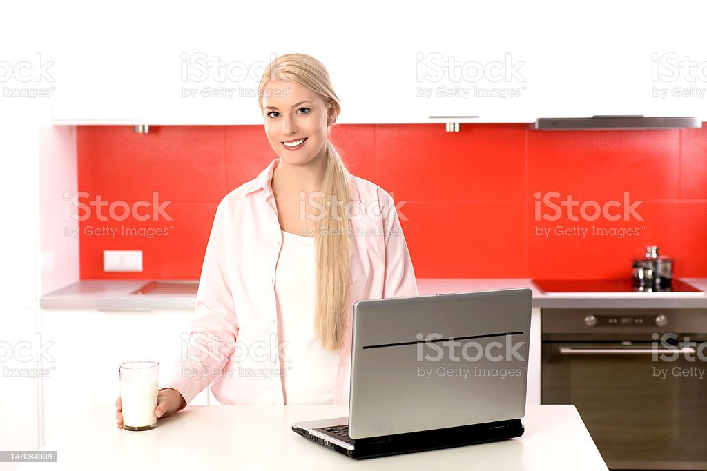 Woman in kitchen with laptop royalty-free stock photo