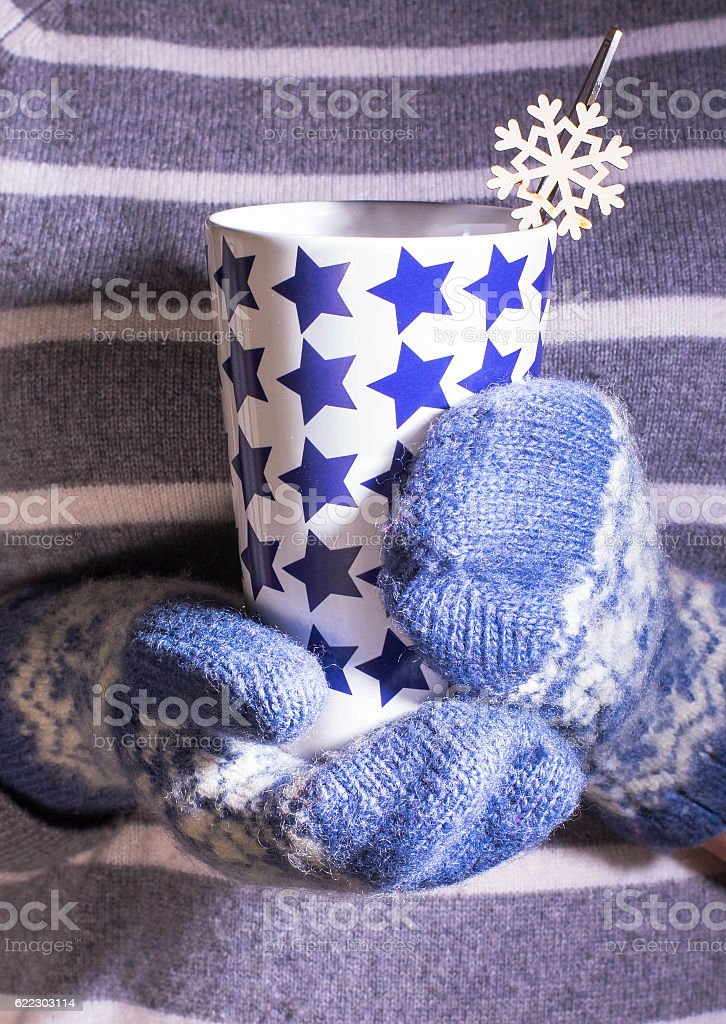 Woman in knit warm mittens with mug stock photo