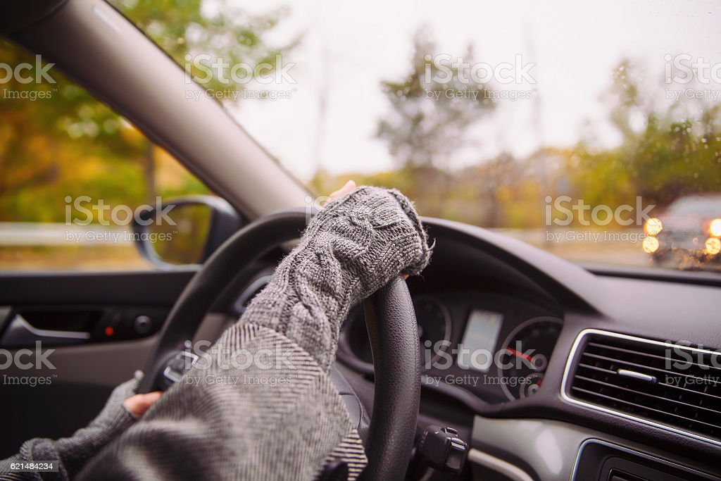 woman in knitted gloves fingerless driving a car stock photo