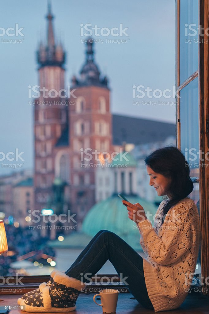 Woman in Krakow texting at the window stock photo