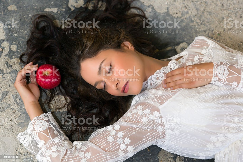 Woman in lace dress with apple stock photo