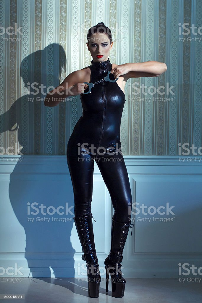 Woman in latex catsuit holding handcuffs royalty-free stock photo