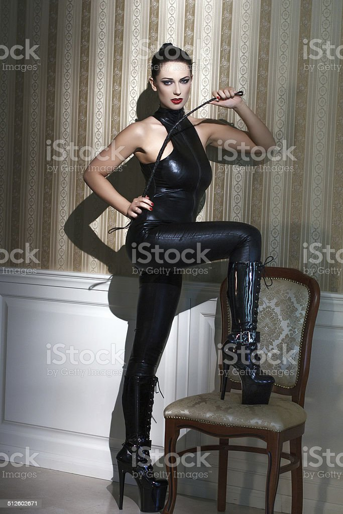 Woman in latex catsuit with whip royalty-free stock photo