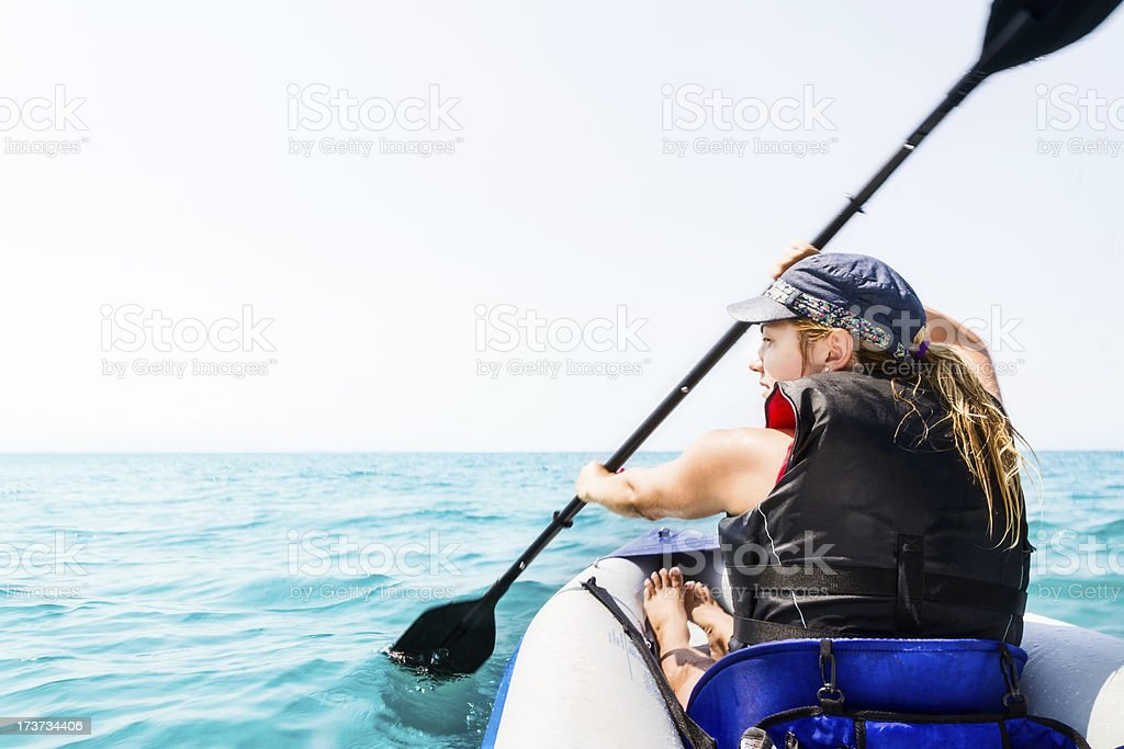 Woman in life vest and blue hat kayaking on the vast sea royalty-free stock photo
