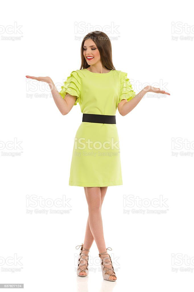 Woman In Lime Green Dress Presenting stock photo