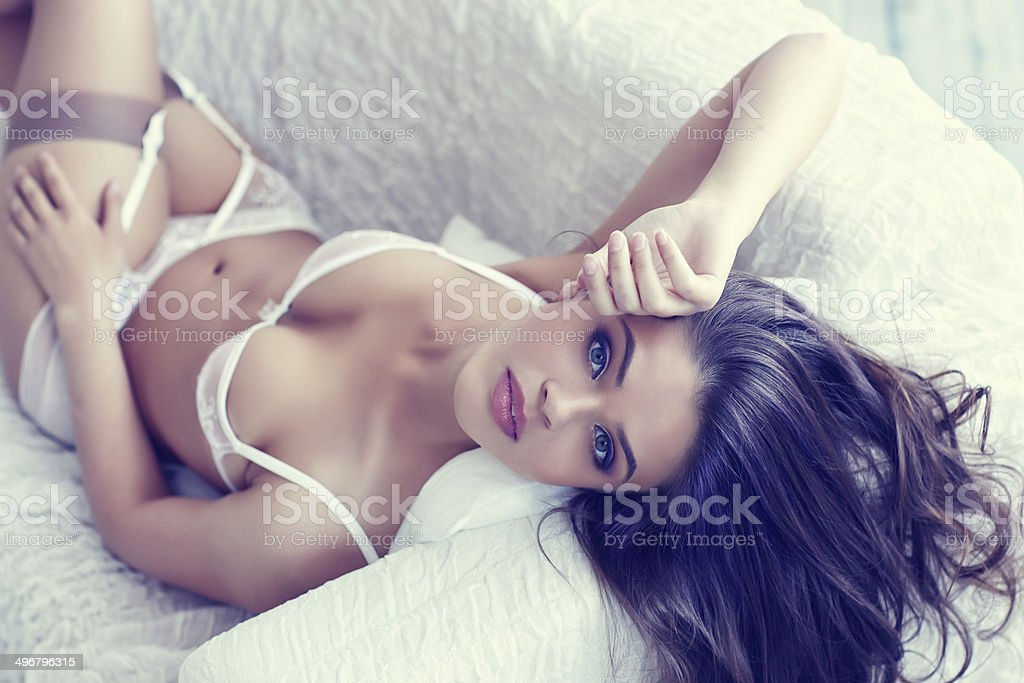 Woman in lingerie on couch stock photo