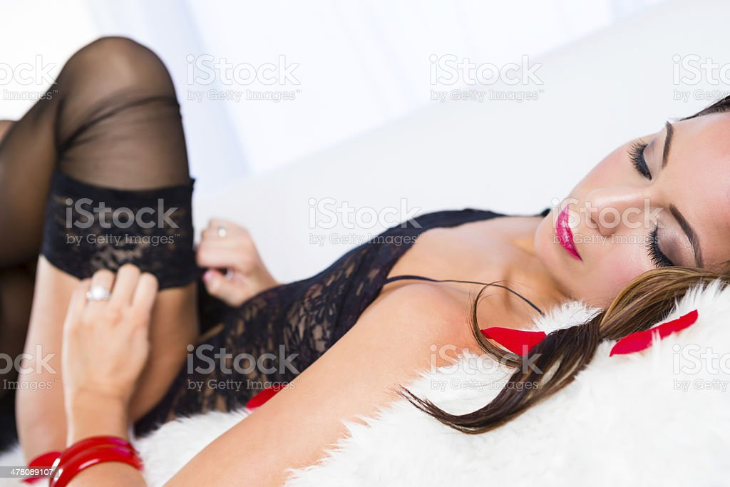 Woman in lingerie pulling up stocking stock photo