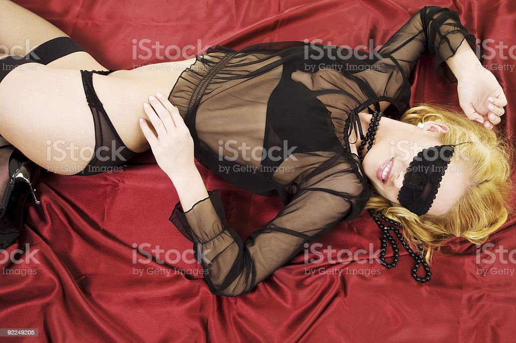 Woman in lingerie wearing a black mask lying on the bed royalty-free stock photo