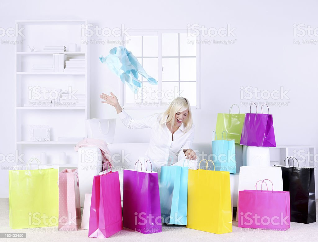 Woman in living room opening presents surrounded by gift bags royalty-free stock photo