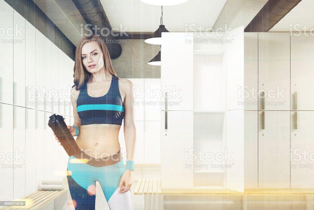 Woman in locker room with open door, toned stock photo