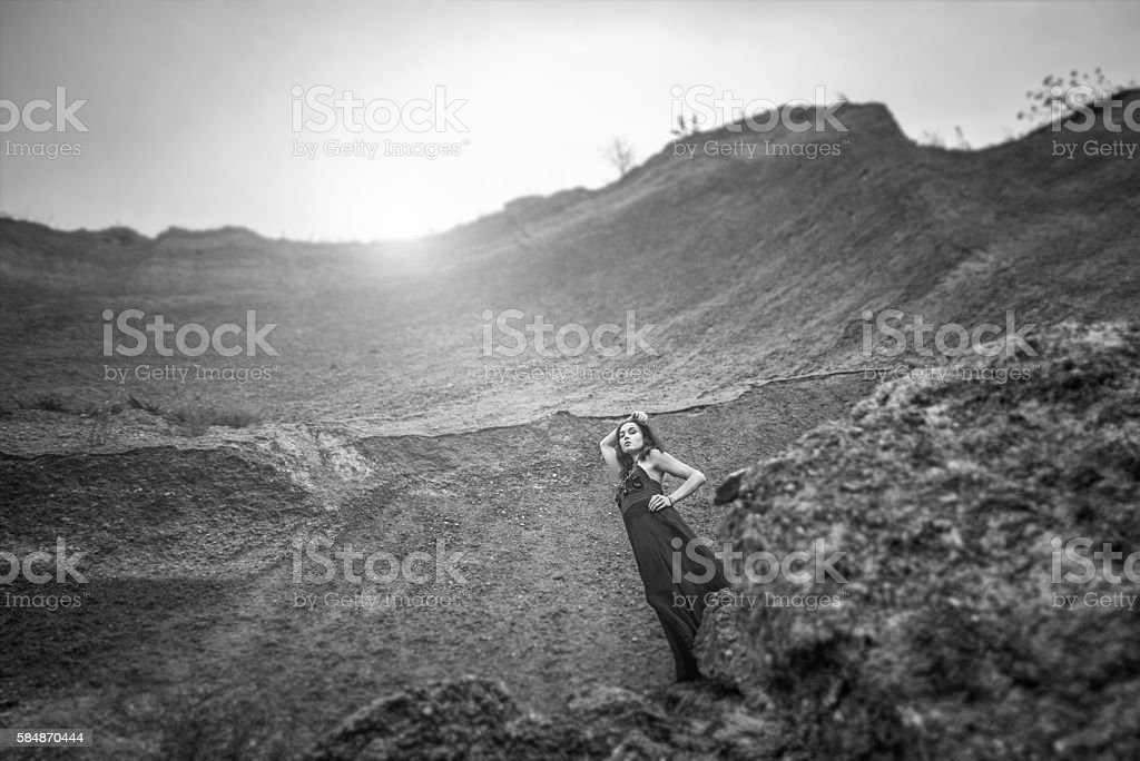 Woman in long black dress on the sand canyon stock photo