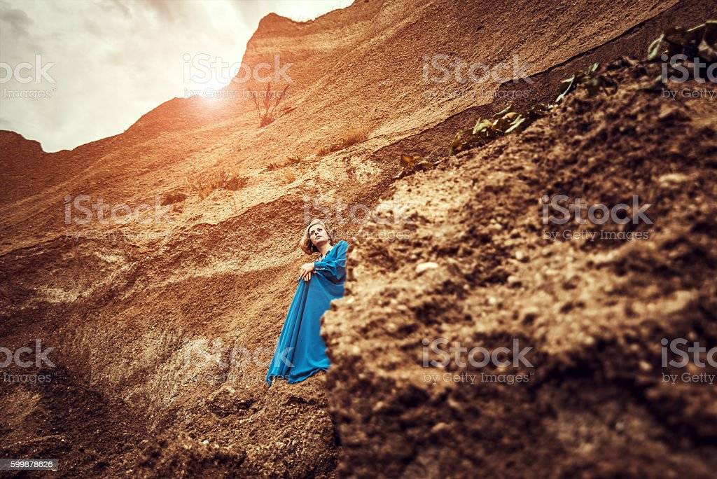 Woman in long blue dress on the sand canyon stock photo