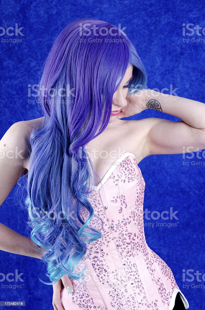 Woman in long blue/purple wig looking down. royalty-free stock photo