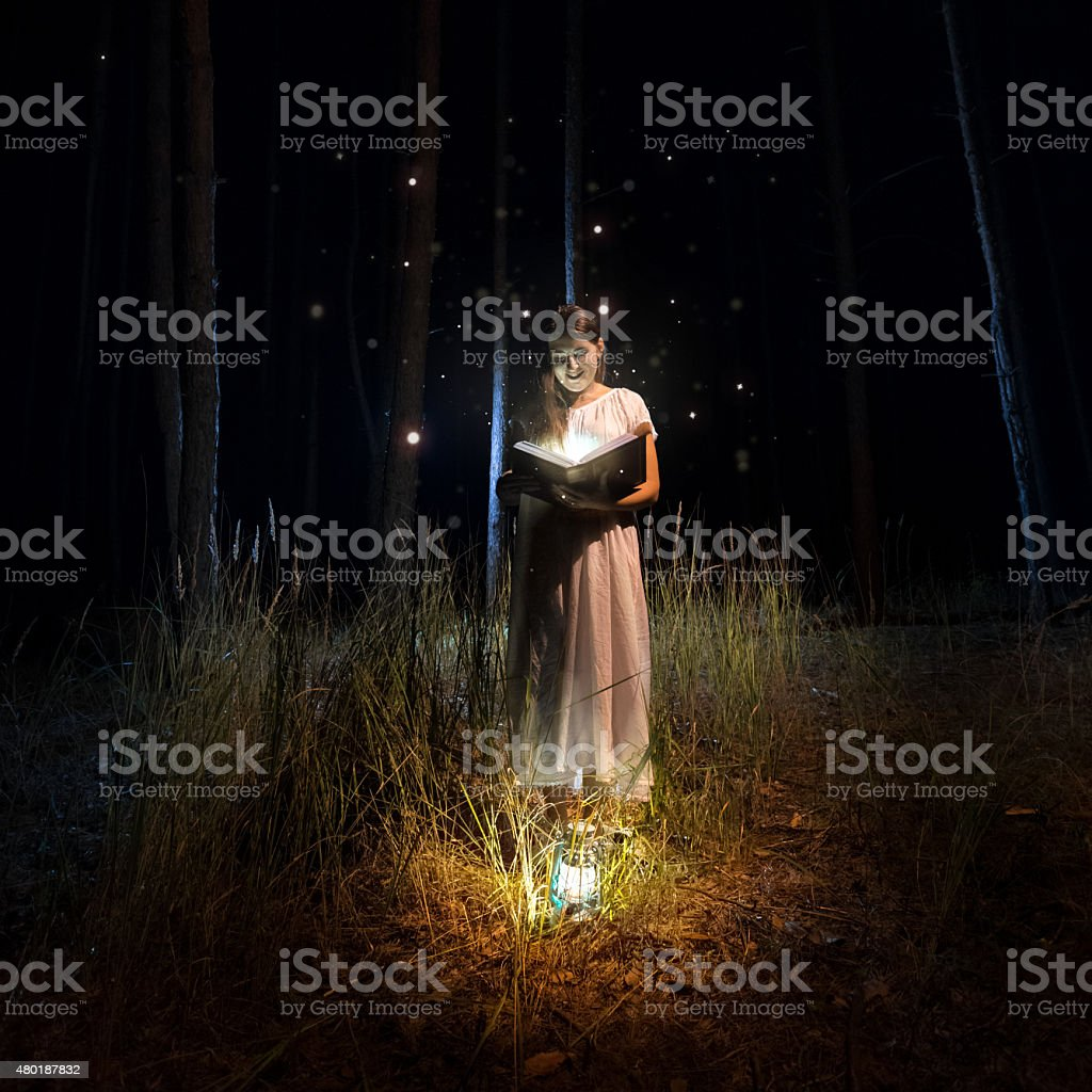 woman in long dress reading old book at mysterious forest stock photo