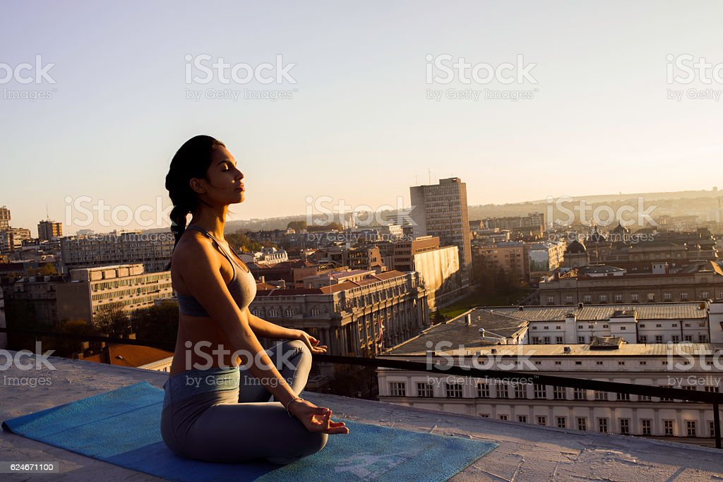 woman in lotus position meditating on the rooftop stock photo