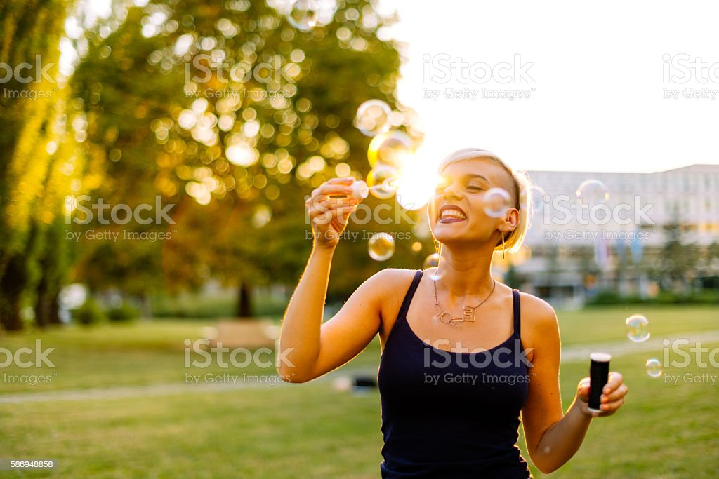 Woman in love, blowing bubbles in summer sunset stock photo