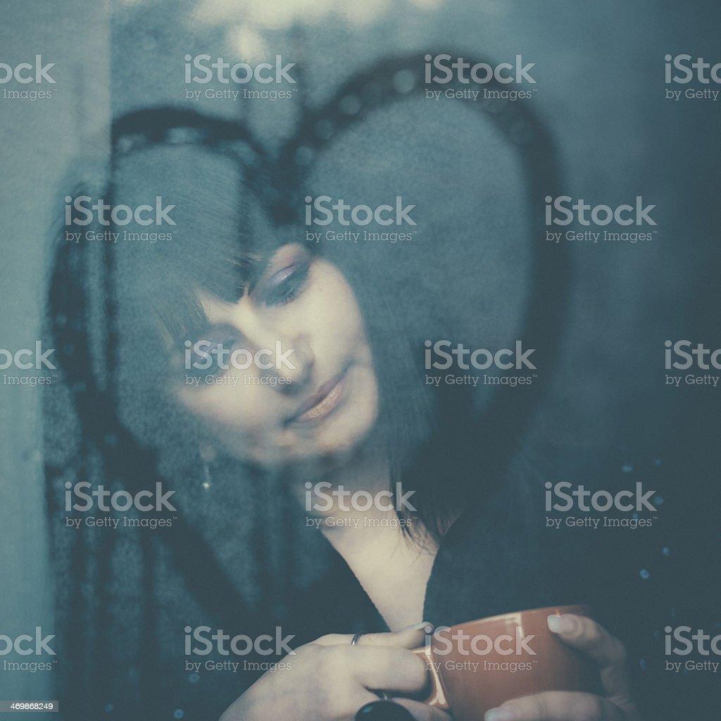 Woman in love looking through window stock photo