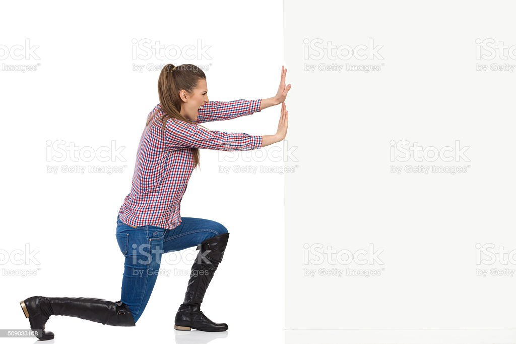 Woman In Lumberjack Shirt Pushing Wall stock photo