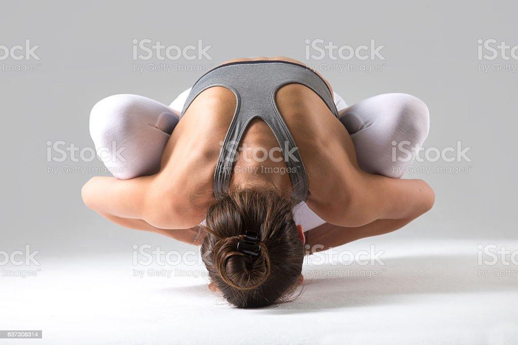 Woman in Malasana with forward bend pose, grey studio background stock photo
