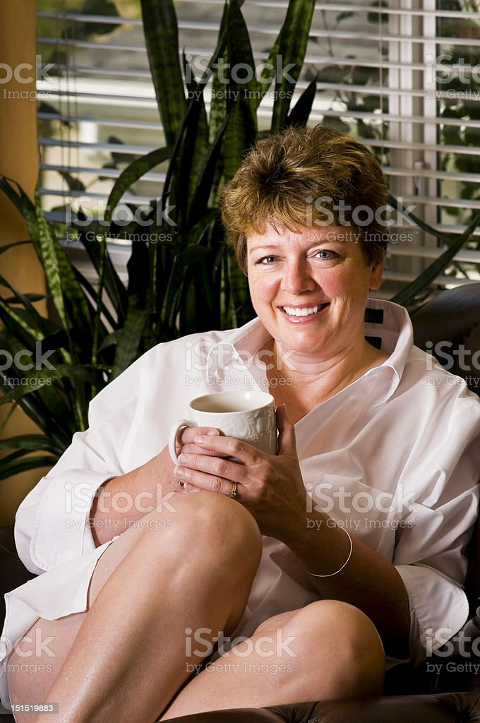 Woman in man's white shirt drinking coffee royalty-free stock photo