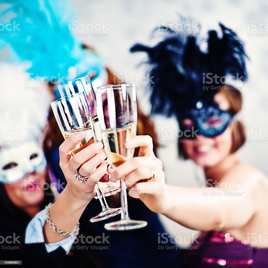 Woman in masks and drinking champagne stock photo