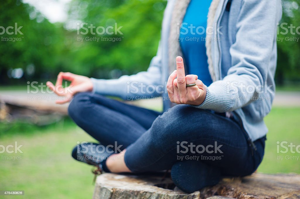 Woman in meditation pose displaying rude gesture stock photo
