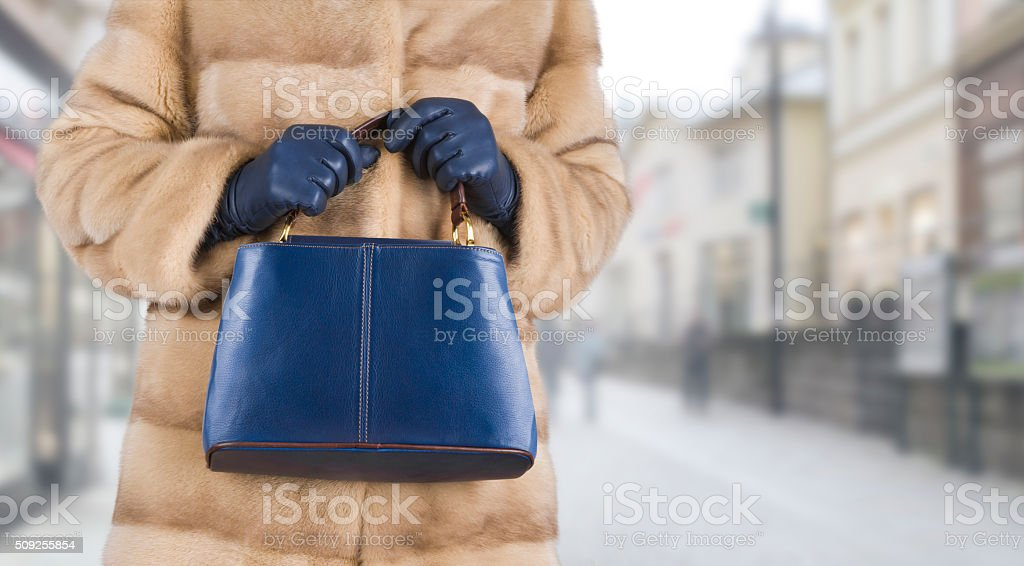 Woman in mink fur coat holding leather bag in hands stock photo