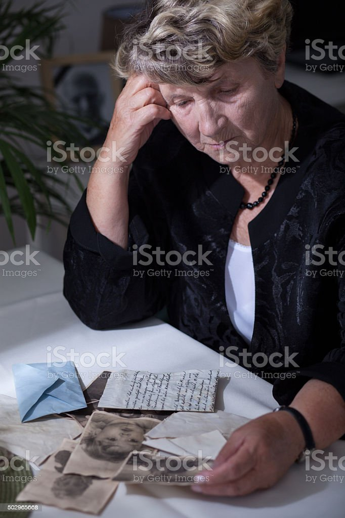 Woman in mourning watching photos stock photo