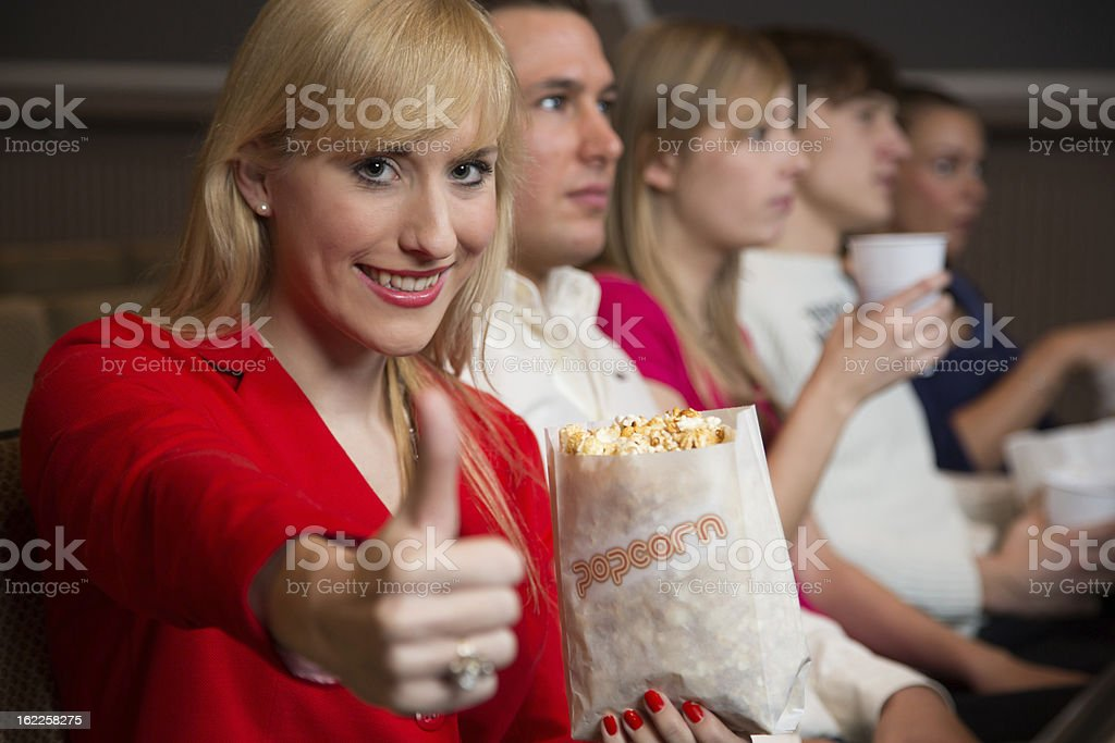woman in movie theatre showing thumbs up royalty-free stock photo