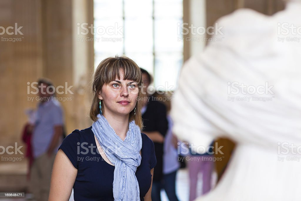 Woman in museum looking at fine art statue stock photo
