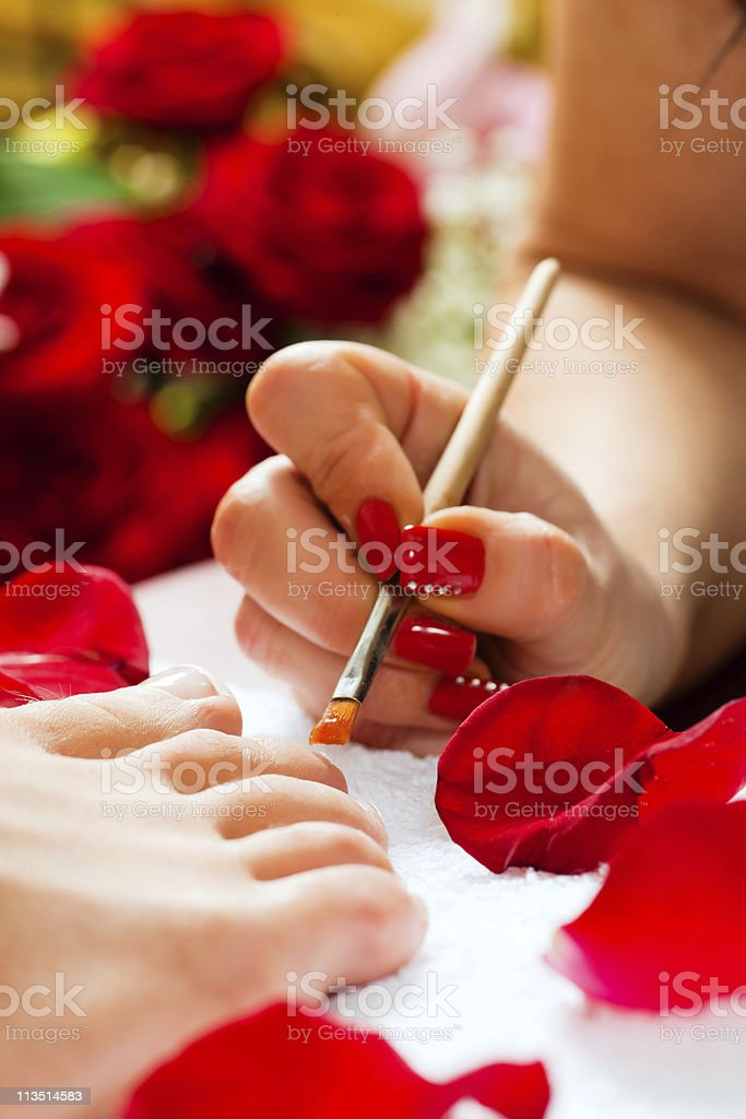 Woman in nail studio receiving pedicure royalty-free stock photo