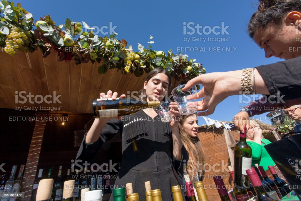 Woman in national Georgian costume pours wine into a glass during festival stock photo