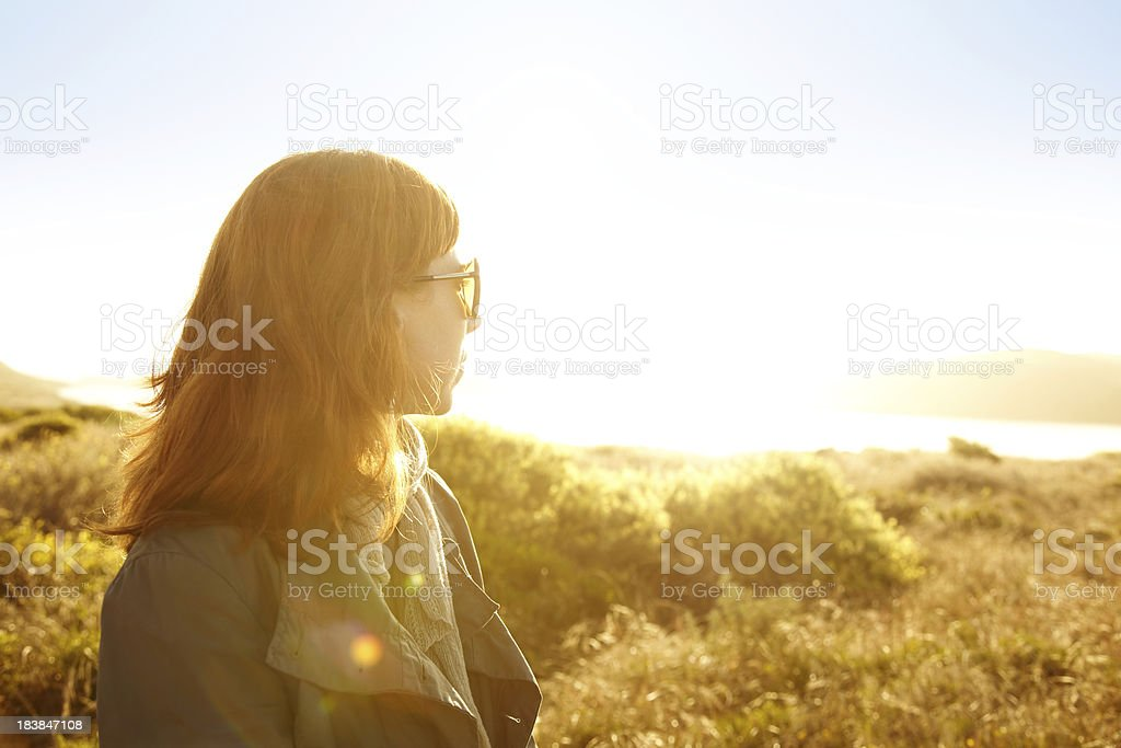Woman in nature backlit by sun looking at ocean royalty-free stock photo