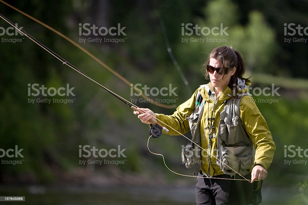 Woman in nature fly fishing for trout wearing sunglasses stock photo