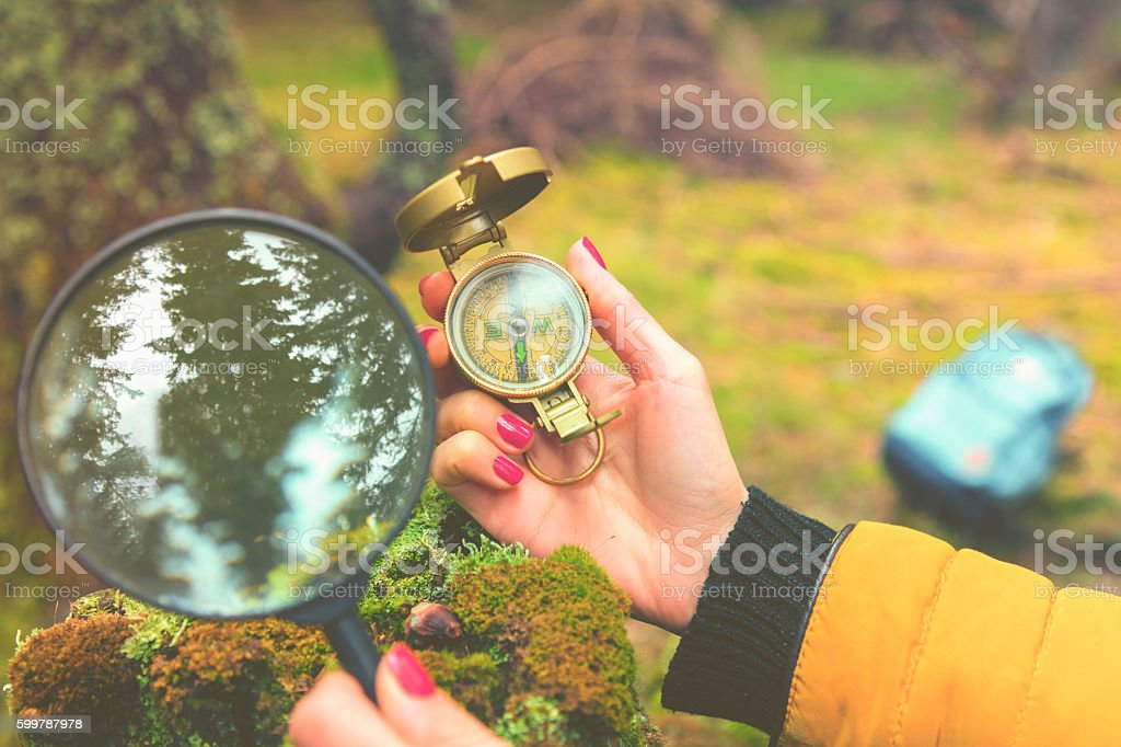 Woman in nature holding compass and magnifying glass. stock photo