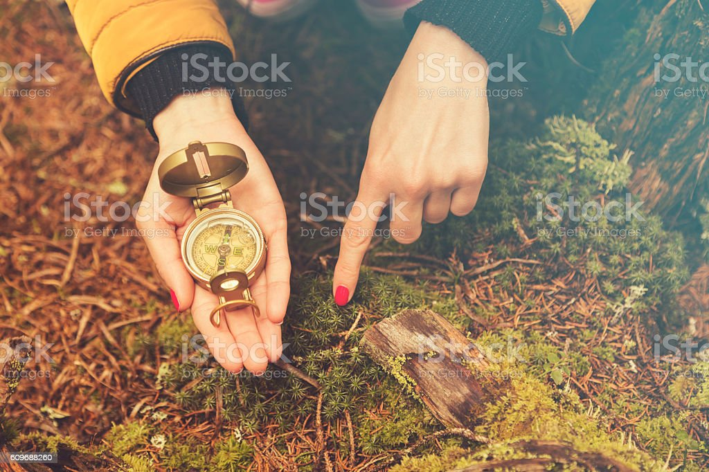 Woman in nature holding compass. stock photo