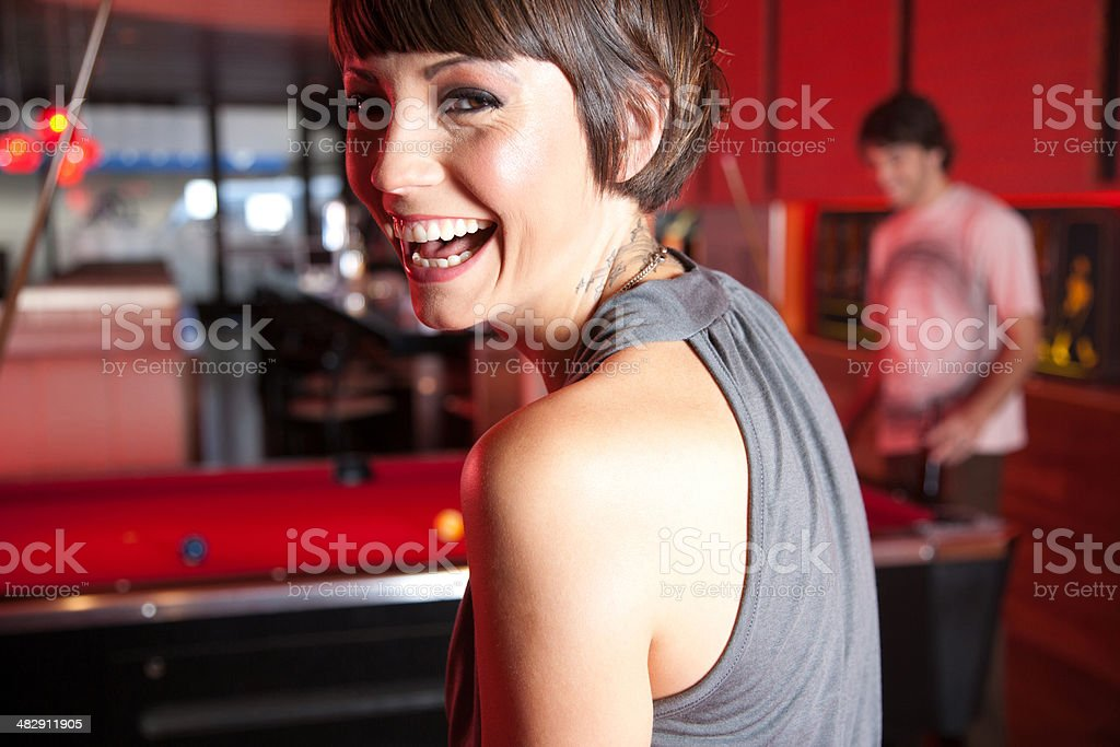 Woman in nightclub standing by pool tables smiling stock photo