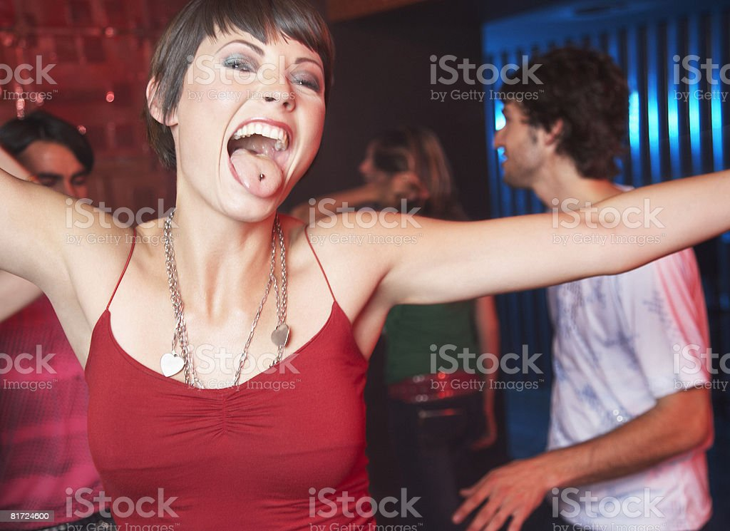 Woman in nightclub sticking her tongue out with people dancing behind her smiling royalty-free stock photo