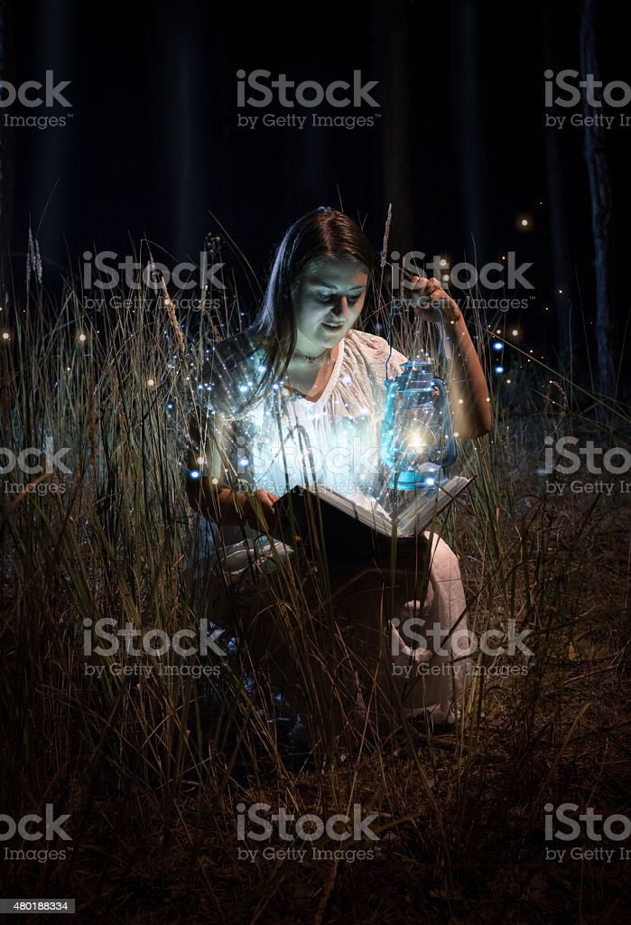 woman in nightgown sitting at field at night and reading stock photo