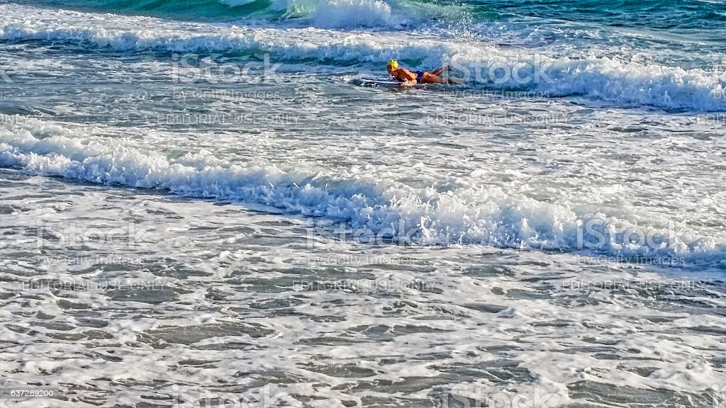 Woman in Ocean with Surfboard stock photo