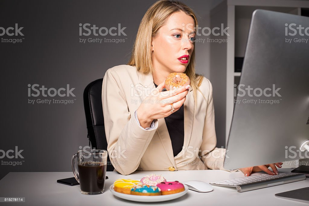 Woman in office eating junk food stock photo
