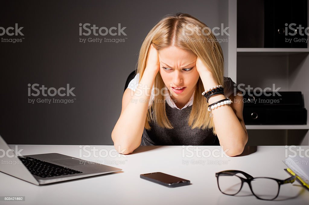 Woman in office holding her head in disgust stock photo