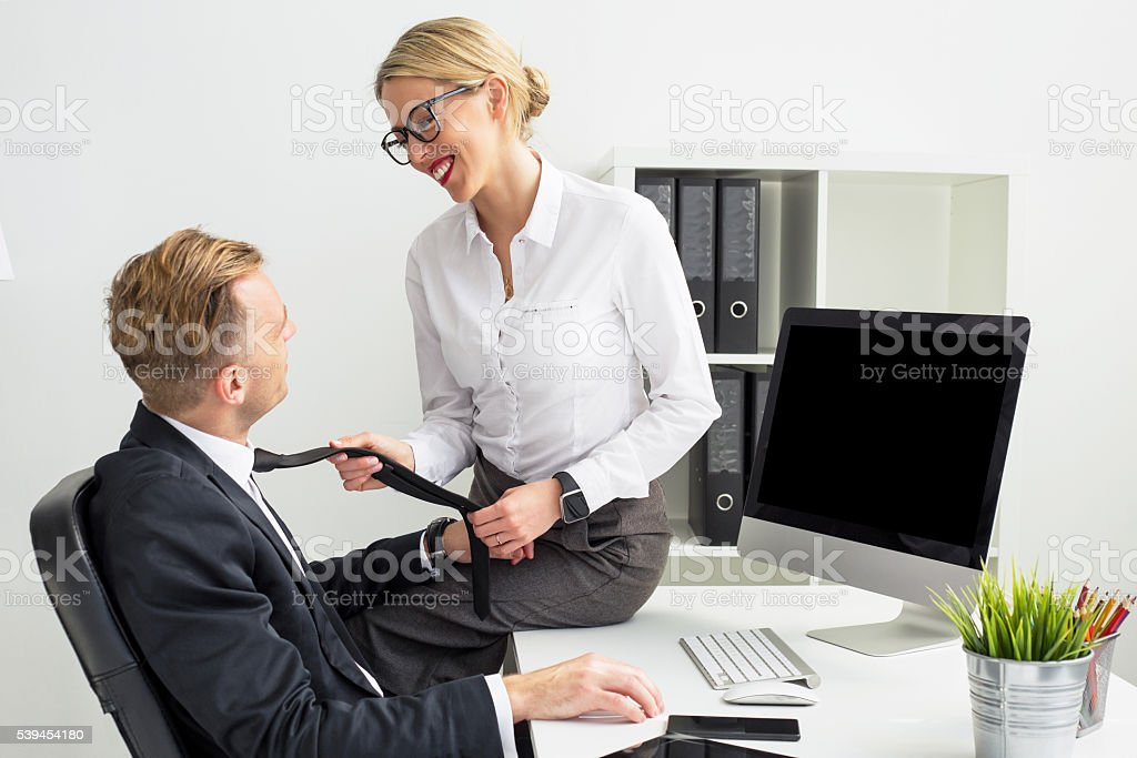 Woman in office pulling mans tie stock photo