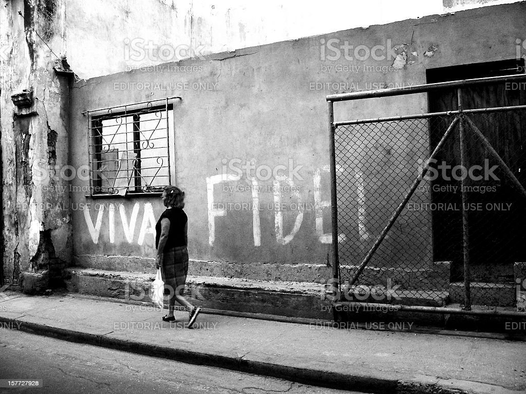 Woman in old Havana passing a wall 'Viva Fidel ' stock photo