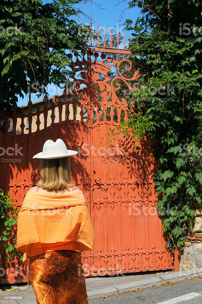 Woman in orange and old gate royalty-free stock photo