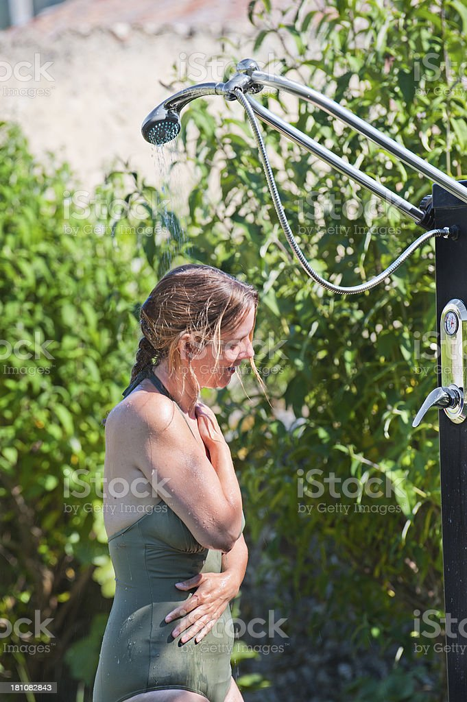 Woman in outdoor shower stock photo