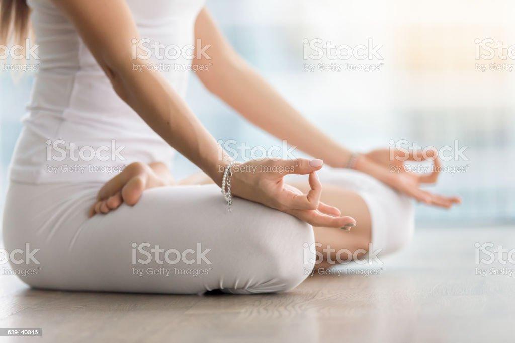 Woman in Padmasana pose with mudra against floor window, closeup stock photo