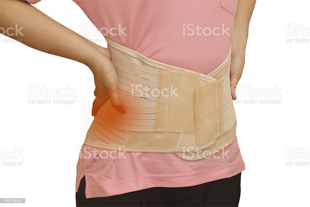 Woman in pain from back injury wearing lumbar brace corset royalty-free stock photo